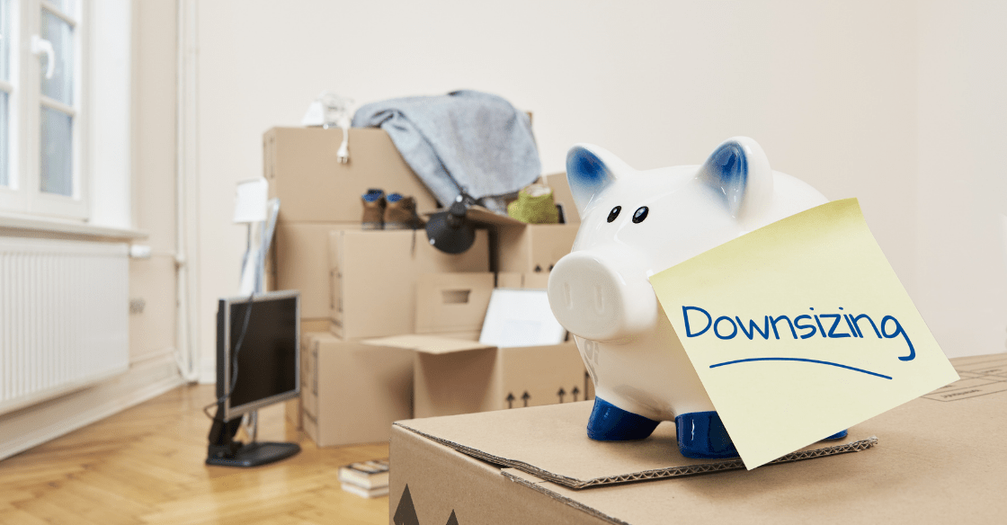 Stacked and packed moving boxes with a piggy bank. The concept of downsizing your home.